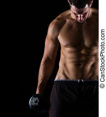 Strong muscular man holding dumbbell on black