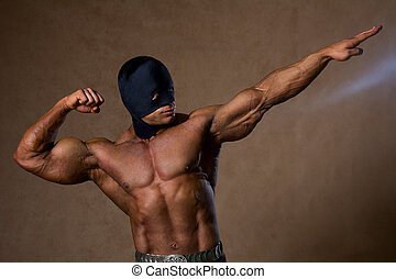 Strong muscular man in black mask and with a naked torso