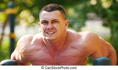 Strong muscular man workout in the park