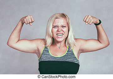 Strong muscular sporty woman flexing muscles