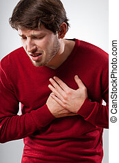 Strong pain - Young man in red sweater has a strong chest...