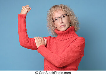Strong powerful woman raises arms and shows biceps