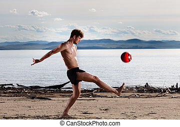 strong sexy male kick red ball on the beach
