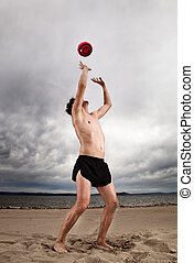 strong sexy male with red ball on the beach