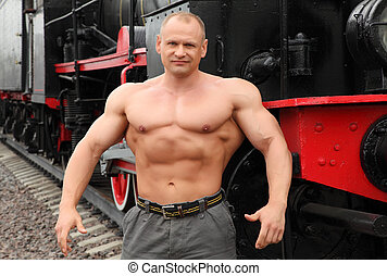 strong shirtless man against locomotive