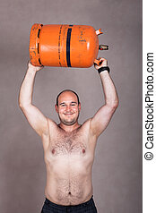Strong shirtless man lifting a gas bottle