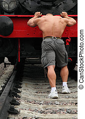 strong shirtless man pushs locomotive