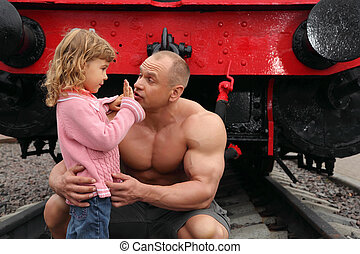 strong shirtless man sits on railroad with little girl