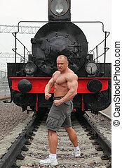 strong shirtless man stands on railroad against locomotive