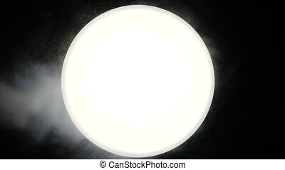 Strong smoke blows on a white ball against a dark background. Someone gives steam to a bright mystical circle in a black background. The ball is similar to the moon and causes various associations.