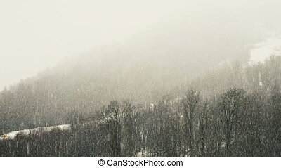 Strong snowfall in the mountains, snow falls by a wall