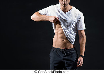 Strong sportsman boasting of his perfect figure