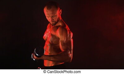 Strong sportsman lifting heavy dumbbell in smoke