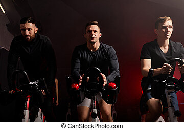 strong sportsmen on gym bicycle, training on a stationary bike in health club