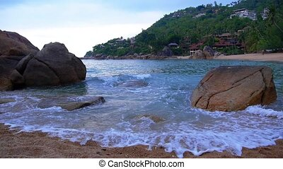 Strong Waves Splashing Against the Rocks. Amazing Beach Panorama of Luxury Villas and Bungalows with Sea View.