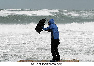 A woman in a blue raincoat holding a black umbrella struggles with the umbrella due to stormy, windy weather on a beach