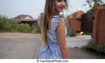strong wind blows pretty lady fair hair wearing blue dress -...