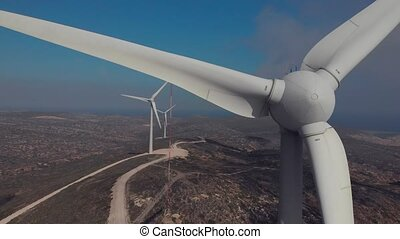 strong wind rotates large windmill blades on seashore close...