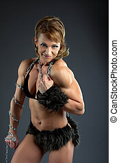 Strong athletic woman body builder posing in amazon fur costume with chain
