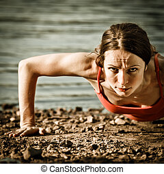 Strong woman doing pushups at the beach