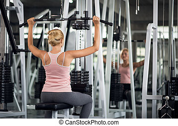 Strong woman exercising with pulldown machine in a fitness...
