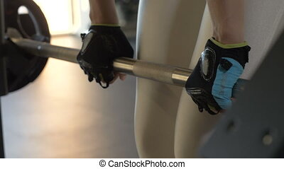 Strong woman leaning with heavy barbell for training buttocks in modern fitness club