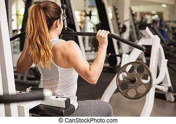 Strong woman on a lat pulldown machine - Rear view of a...