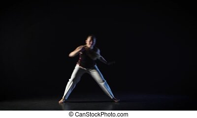 Strong woman performing incredibly complex of martial art of...