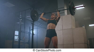 Strong Woman Weightlifting. Athletic Beautiful Woman Does Overhead Deadlift with a Barbell in the Gym. Gorgeous Female Professional Bodybuilder Workout Weight Lift Exercises in the Authentic Fit. High quality 4k footage