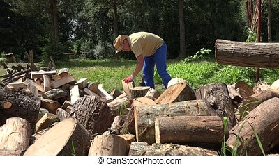 Strong worker man chop firewood, leave axe and walk away. 4K