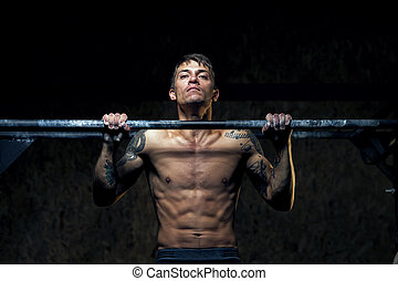 Strong young man doing pull up exercise in gym
