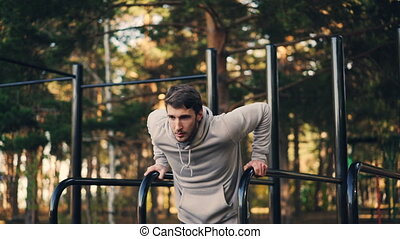 Strong young man is doing triceps dips on parallel bars in city park exercising outdoors in the morning in summer. Active lifestyle, workout and nature concept.