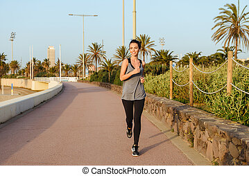 Strong young sports woman running outdoors