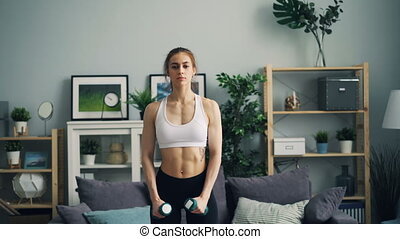 Strong young woman in sportswear doing exercises with dumbbells in apartment