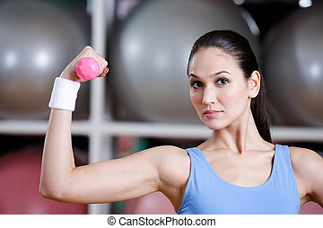 Strong young woman training with dumbbells
