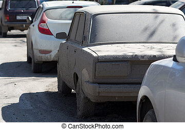 strongly dirty car parked on a city street