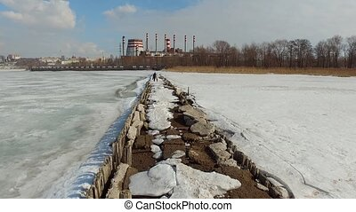 Destroyed structure on frozen pond near factory