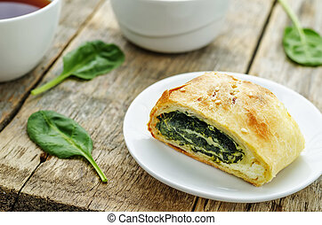 strudel with spinach and ricotta on a dark wood background....