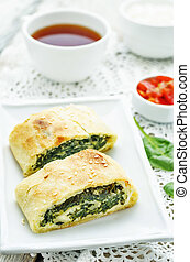 strudel with spinach and ricotta on a white background. the...