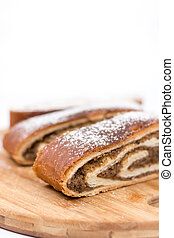 Strudel with walnuts and sugar on the round wooden board