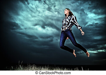 struggle - Beautiful young woman jumping in the field over...