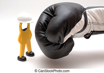 boxing-glove threatening the figure of a worker with helmet