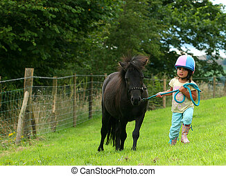Struggling - Little girl in a pink and blue silk riding hat...