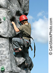 Struggling - Boy climbing on a training rock face, wearing a...