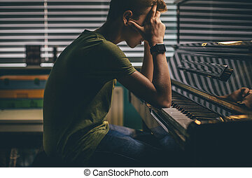 Struggling to Learn - Teenager sitting at his piano with his...