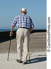 Rear view of an elderly man walking with walking sticks on a beach promenade.