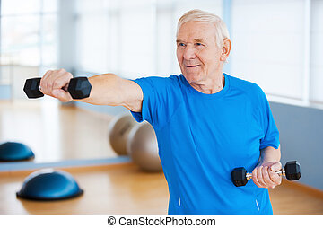 Struggling with age. Confident senior man exercising with dumbbells and smiling while standing in health club