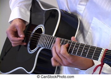 Strumming - A man strums an black acoustic guitar with a...