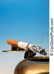 Stub of a cigarette on a bronze ashtray