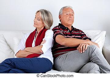 Stubborn Couple on Sofa - Senior couple sitting on sofa...